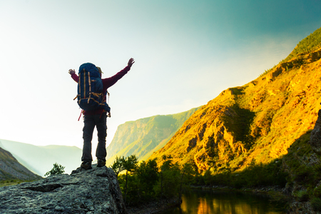 Hiker with backpack stands on the rock with raised hands and enjoys sunrise valley views. Altai, Russia Stok Fotoğraf