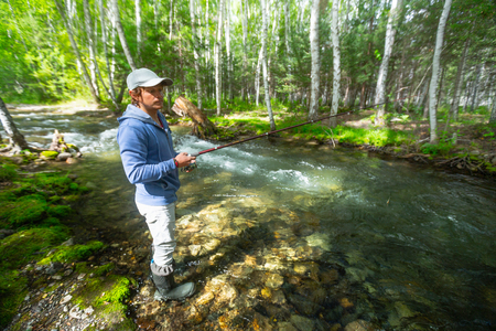 Young amateur angler fishing in the small rapid river in the forest. Altai, Russia Stok Fotoğraf