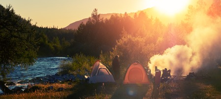 Panorama of the camp in the wild area. Hikers set the tents near the river and make fire at sunset