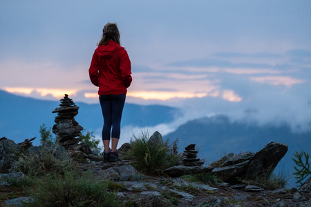 Young woman in red stands near the cairns and looks into the valley at sunset. Altai Republic, Russia. Image has some noise Stock Photo