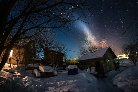 Night view of the winter yard with wooden highlighted buildings and starry sky Stok Fotoğraf