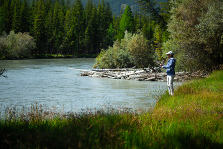 Young adult angler fishing on the river. Altai, Russia