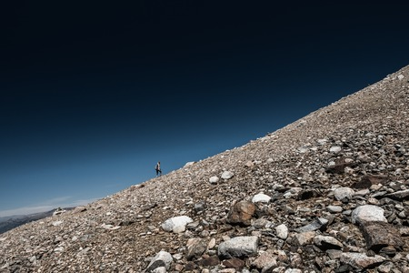 Lady hiker climbs rocky hill of the Cerro Castillo Mountain, Chilean Patagonia.