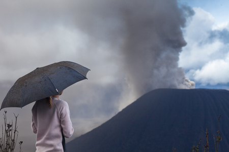 Woman with umbrella covered with ash watches volcano eruption. Indonesia