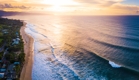 view of the North Shore of Oahu at sunset. Area of Banzai Pipeline surf spot (breaking wave on the foreground at the right is Pipeline). Hawaii, USA Stock Photo