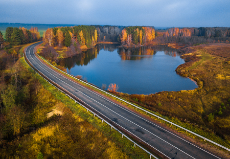 Asphalt road curves near the small lake with colorfull autumn trees on its coast