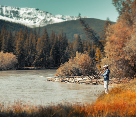 Young amateur angler fishing in the rapid river with snow caped mountains on the background. Altai, Russia. Version of the file with tilt shift effect applied. Stock fotó