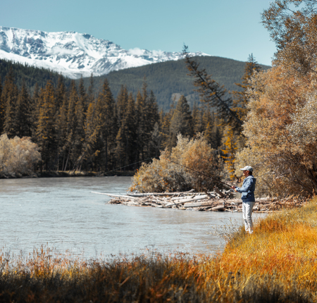 Young amateur angler fishing in the rapid river with snow caped mountains on the background. Altai, Russia. Stok Fotoğraf