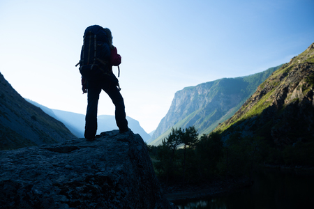 Woman hiker stands with backpack on the rock and enjoys the mountains view. Altai, Russia