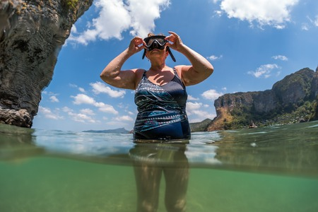 Woman in years going to immerse underwater and snorkling in the sea