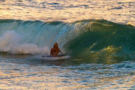 OAHU-USA, 03 NOVEMBER 2018: Little boy surfs barelling wave at famous Pipeline surfspot at smaller swell