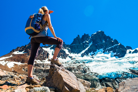 Woman hiker stands on the rocks and enjoys glacier view of the Cerro Castillo Mountain, Patagonia, Chile. Stock Photo - 114554205