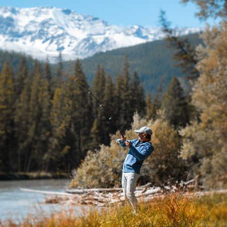 Young amateur angler fishing in the river with snow caped mountains on the background. Altai, Russia. Stok Fotoğraf