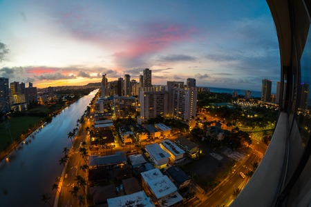 The city of Honolulu at sunrise with part of the balcony with city reflection visible in the frame. Hawaii, USA