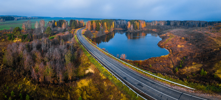 panorama of the asphalt road curving near the small lake with colorfull autumn trees on its coast