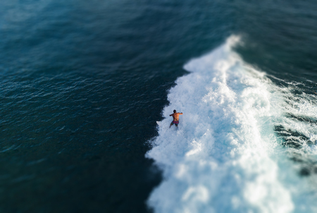 Aerial view of the surfer riding the ocean wave. Oahu, Hawaii. Tilt shift effect applied Stock fotó