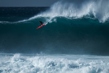 Extreme surfer rides gigantic ocean wave at Waimea Bay surf spot. The North Shore of Oahu, Hawaii