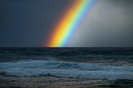 Rainbow over the rough Pacific Ocean with the North Shore waves on the foreground. Oahu, Hawaii Stock Photo