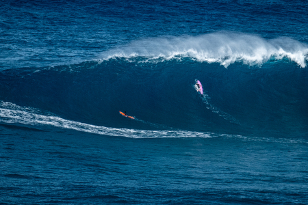 Two big wave surfers paddle to line up and pass huge ocean wave of Jaws (Peahi) surf spot on Maui, Hawaii.