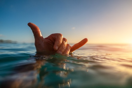 Surfer shows Hawaiian Shaka sign being in the water at sunset Banco de Imagens