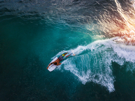 Bodyboard surfer rides tropical wave at sunset Stock Photo