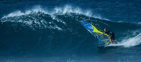 MAUI  USA - 21 DECEMBER 2018: Windsurfer rides ocean wave at Hawaiian Hookipa surf spot