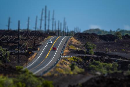 Two cars meet on the Mamalahoa Highway (Hawaii Belt Road) in Kau district with black lava fields around. Hawaii, USA 스톡 콘텐츠