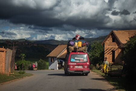 FIANARANTSOA  MADAGASCAR - 23 DECEMBER 2013: Loaded African bus moves on the paved road and passes villagers with mountains on the background Editöryel