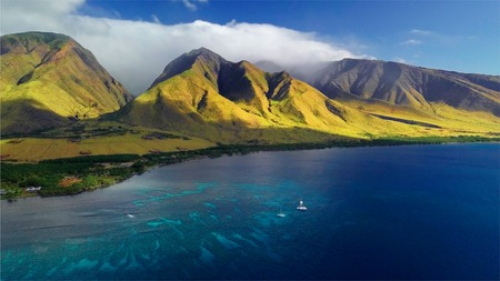 Aerial view of the west coast of Maui with visible coral reef and green mountain on the background. Area of Olowalu, Hawaii Фото со стока