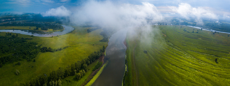Aerial panorama of the white fluffy cloud hanging over green summer fields and curved river