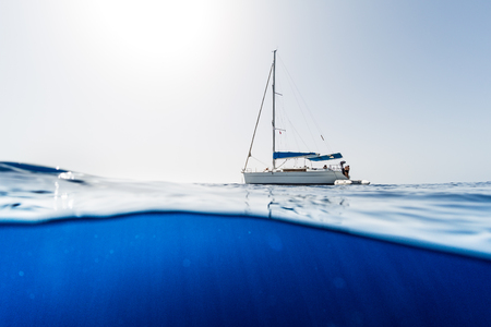 Split shot of the sailing boat in the open sea with clear blue underwater view
