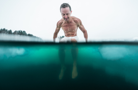 Young man with lean muscular body sits on the ice and going to swim in the cold winter water. Splitted image with underwater view of the ice hole