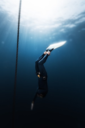 Freediver in monofin descends into depth along the anchor chain in the sea. Version of the photo with the tilt shift effect applied Stock Photo
