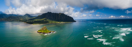 Aerial panorama of the island Mokolii (Chinaman's Hat) surrounded by torquise ocean waves and mountains of the East Coast of Oahu, Hawaii.