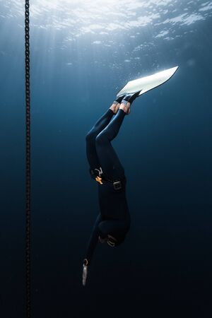 Freediver in monofin descends into depth along the anchor chain in the sea