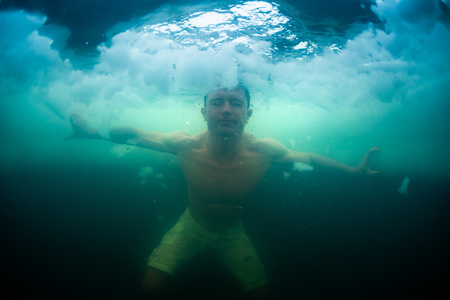 Young man haves recreational winter swim in the lake. Underwater view with ice floating around Stok Fotoğraf