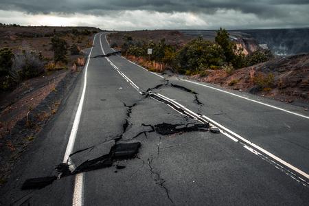 Uszkodzona droga asfaltowa (Crater Rim Drive) w Parku Narodowym Hawaii Volcanoes po trzęsieniu ziemi i erupcji wulkanu Kilauea (dymy w prawym górnym rogu) w maju 2018 r. Big Island, Hawaje