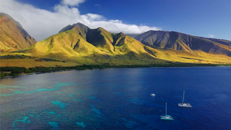 Aerial view of the west coast of Maui with visible coral reef, sailing boats and green mountain on the background. Area of Olowalu, Hawaii