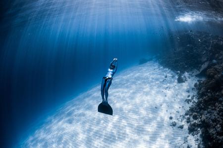 Woman freediver in monofin glides in the depth over the sandy bottom and looks at the surface Фото со стока