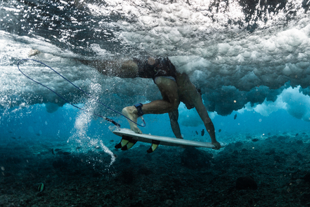 Surfer performs dive with his surfboard (Duck Dive) under the powerful wave at shallow reef area