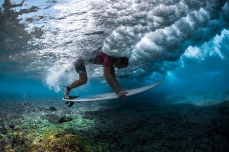 Surfer dives under the wave with the surfboard to safely pass it and performs the Duck Dive trick