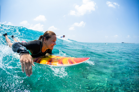 Happy lady surfer paddling and going to take the tropical wave at sunny day Stockfoto