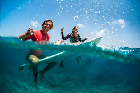 Young couple of surfers having fun in the tropical ocean