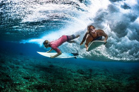 Two young surfers man and woman survive under the breaking ocean wave