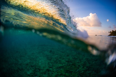 Ocean wave breaking over the reef at sunset Banque d'images