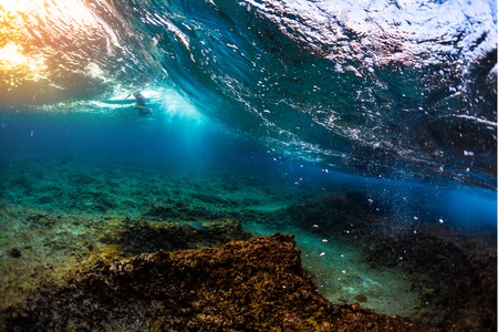Underwater view of the ocean wave breaking over the shallow reef with sharp stones. Surfer floats on the background