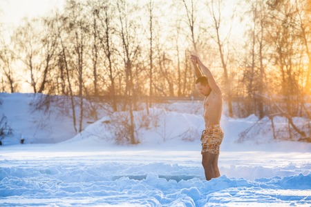 Semi naked man does exercises and meditates in the winter field with sun shining through the trees