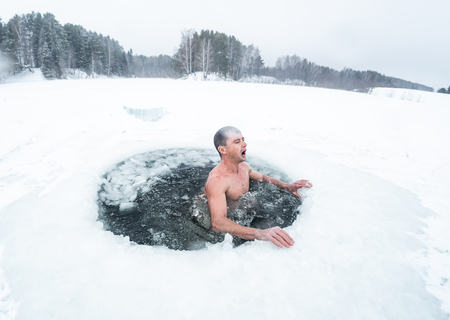 Young man haves recreational winter swim in the lake Foto de archivo - 120631713