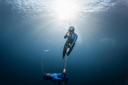 Zwei Freitaucher spielen mit Blasen in der Nähe des Seils