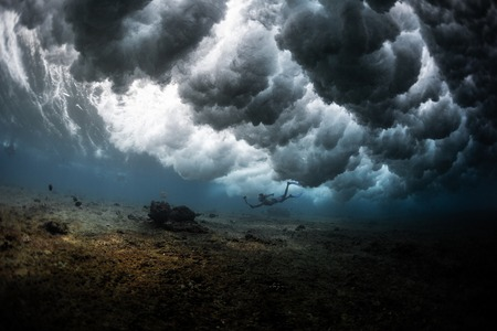 Young man dives under the powerful ocean wave breaking over him in a form of clouds and shots selfie Banco de Imagens